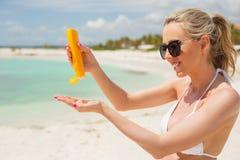 Kvinna som använder sunscreen på stranden Arkivfoton