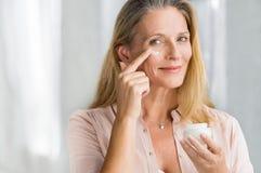 Kvinna som applicerar anti-åldras lotion på framsida royaltyfri foto