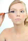 Kvinna som applicerar blå mascara Fotografering för Bildbyråer