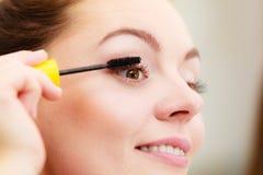 Kvinna som applicerar blåtiramascara till hennes ögonfrans Arkivbilder