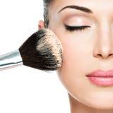 Kvinna som applicerar det torra kosmetiska tonala fundamentet på framsidan Royaltyfri Bild