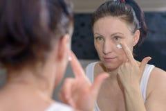 Kvinna som applicerar en fuktakräm till hennes kind Royaltyfri Fotografi