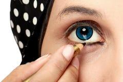 Kvinna som applicerar eyeliner Arkivbild