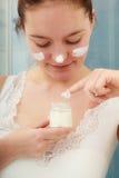 Kvinna som applicerar fukta hudkräm Skincare Arkivbild