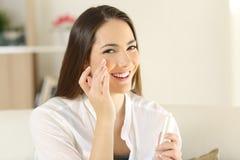 Kvinna som applicerar fuktighetsbevarande hudkrämkräm på framsidan royaltyfria foton