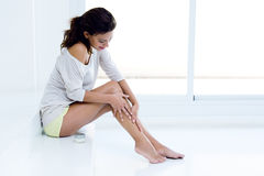 Kvinna som applicerar kräm på ben Arkivfoton