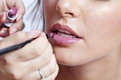 Kvinna som applicerar läppstift royaltyfri foto