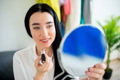 Kvinna som applicerar läppstift arkivbild