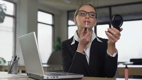 Kvinna som applicerar läppstift i arbetsplats, begrepp av klänningen och utseendemässig kod lager videofilmer