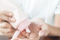 Kvinna som applicerar lotion på hennes hand, skönhetbegrepp arkivbild