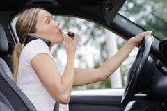 Kvinna som applicerar makeup, medan köra bilen arkivfoto