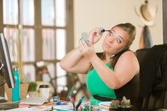 Kvinna som applicerar makeup på hennes skrivbord royaltyfri fotografi