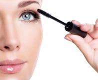Kvinna som applicerar mascara på ögonfrans Arkivbild