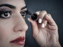 Kvinna som applicerar mascara på henne ögon Fotografering för Bildbyråer