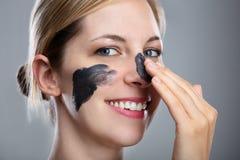 Kvinna som applicerar maskeringen f?r aktiverat kol p? hennes framsida royaltyfri foto