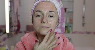 Kvinna som applicerar maskeringen som fuktar hudkr?m Skincare brunnsort Ansikts- maskering royaltyfri bild