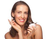 Kvinna som applicerar moisturizing kräm Arkivfoto