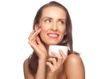 Kvinna som applicerar moisturizing kräm Fotografering för Bildbyråer
