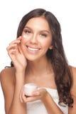 Kvinna som applicerar moisturizing kräm Arkivfoton