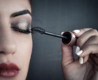 Kvinna som applicerar röd lipstic mascara Arkivfoto