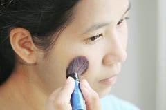 Kvinna som applicerar smink vid rouge Royaltyfri Foto