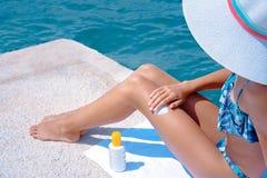 Kvinna som applicerar suncream p? stranden, innan att solbada royaltyfria bilder