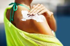 Kvinna som applicerar sunscreen på hennes skuldra arkivfoton