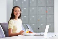 Kvinna som arbetar i designstudion som har lunch på skrivbordet royaltyfri bild