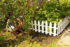 Kvinna som arbetar i trädgården som squatting, hennes kontur som är synlig till och med träden arkivbild