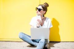 Kvinna som arbetar med bärbara datorn på den gula väggbakgrunden royaltyfri foto
