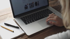Kvinna som arbetar med bärbara datorn som förläggas på träskrivbordet stock video