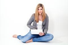Kvinna som arbetar på bärbara datorn, medan sitta på golvet arkivbild