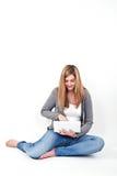 Kvinna som arbetar på bärbara datorn, medan sitta på golvet arkivfoton