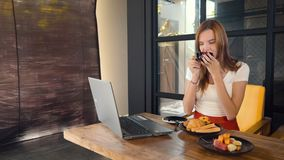 Kvinna som arbetar på bärbara datorn och dricker kaffe i kafé lager videofilmer