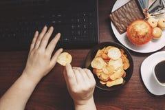 Kvinna som arbetar på datoren och äter chiper Royaltyfri Bild