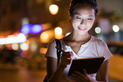 Kvinna som arbetar på den digitala minnestavladatoren på natten arkivfoto