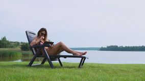 Kvinna som arbetar på en minnestavladator som reser världen på semestern som solbadar på stranden nära sjön arkivfilmer