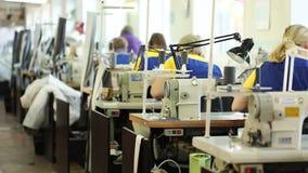 Kvinna som arbetar på en symaskin, industriell formattextilfabrik, arbetare på produktionslinjen, industriell inre stock video