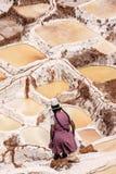 Kvinna som arbetar på salta pannor av Cusco Arkivfoto