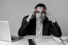 Kvinna som arbetar på skrivbordet för kontor för bärbar datordator i spänningen som lider intensiv huvudvärk och migrän Arkivfoto