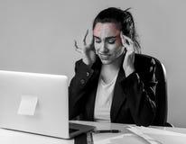 Kvinna som arbetar på skrivbordet för kontor för bärbar datordator i spänningen som lider intensiv huvudvärk och migrän Royaltyfria Bilder