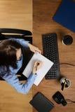 Kvinna som arbetar på skrivbordet som skjutas från över Arkivbild