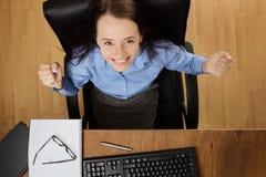 Kvinna som arbetar på skrivbordet som skjutas från över Arkivfoto