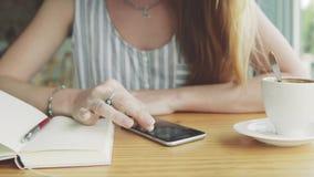 Kvinna som arbetar på smartphonen i kafé med koppen kaffe och anteckningsboken på tabellen lager videofilmer