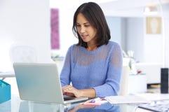 Kvinna som arbetar på bärbara datorn i inrikesdepartementet Royaltyfri Foto