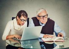 Kvinna som arbetar på bärbara datorn och äldre morfarmanläsning från boken Arkivfoto