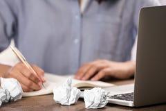 Kvinna som arbetar p? tabellen med skrynkligt papper Utveckling av id? royaltyfria foton