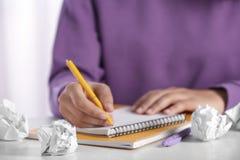 Kvinna som arbetar p? tabellen med skrynkligt papper Utveckling av id? arkivfoto