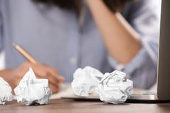 Kvinna som arbetar p? tabellen med skrynkligt papper Utveckling av id? royaltyfri fotografi