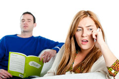 Kvinna som argumenterar på telefonen med mannen som över ser Royaltyfria Foton
